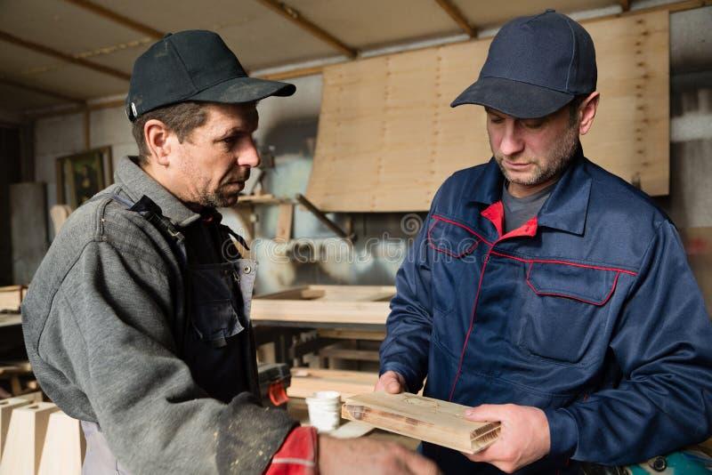 Ξυλουργοί για να συζητήσει την παραγωγή των στοιχείων φιαγμένων από ξύλο στοκ εικόνες