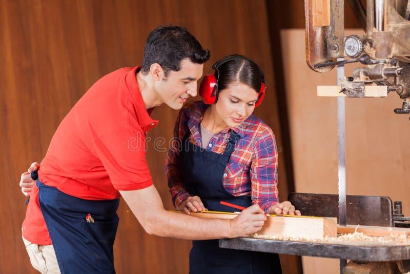 Ξυλουργοί που μετρούν το ξύλο στο εργαστήριο στοκ φωτογραφία με δικαίωμα ελεύθερης χρήσης