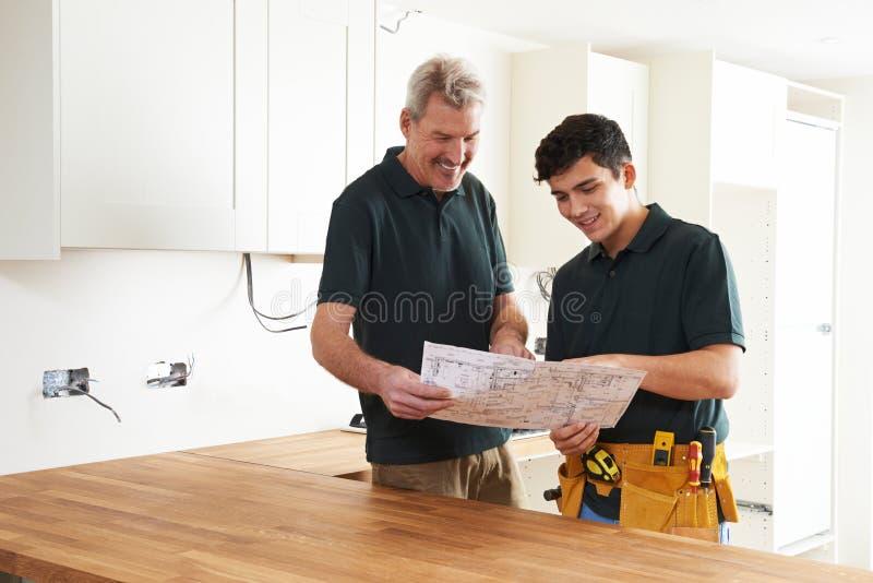 Ξυλουργός και μαθητευόμενος που εγκαθιστούν εγκατεστημένη την πολυτέλεια κουζίνα στοκ φωτογραφίες