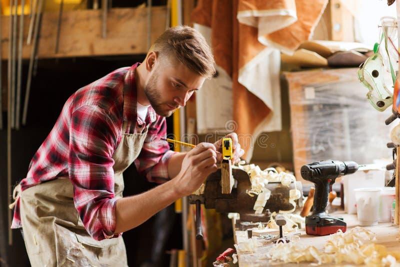 Ξυλουργός με τον κυβερνήτη που μετρά τη σανίδα στο εργαστήριο στοκ εικόνες με δικαίωμα ελεύθερης χρήσης