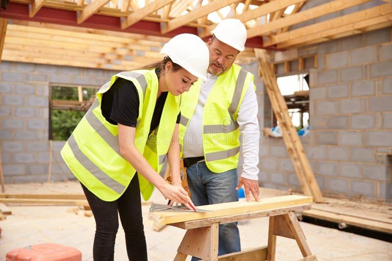 Ξυλουργός με το θηλυκό μαθητευόμενο που εργάζεται στο εργοτάξιο στοκ εικόνα