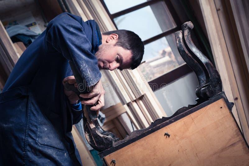Ξυλουργός που αποκαθιστά τα ξύλινα έπιπλα στοκ εικόνες