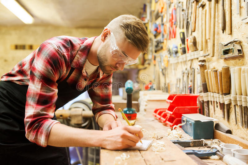 Ξυλουργός που γράφει στο σημειωματάριο στο εργαστήριο στοκ εικόνα με δικαίωμα ελεύθερης χρήσης