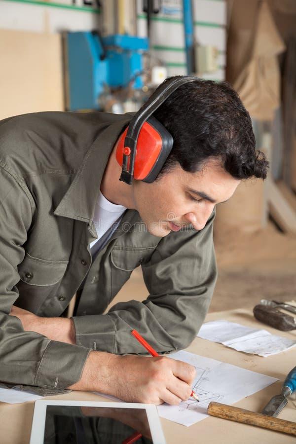Ξυλουργός που εργάζεται στο σχεδιάγραμμα στο εργαστήριο στοκ εικόνες