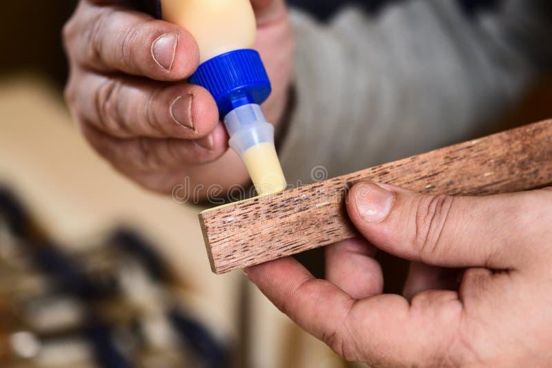 Ξυλουργός που εφαρμόζει την κόλλα στην ξύλινη λεπτομέρεια στοκ εικόνα