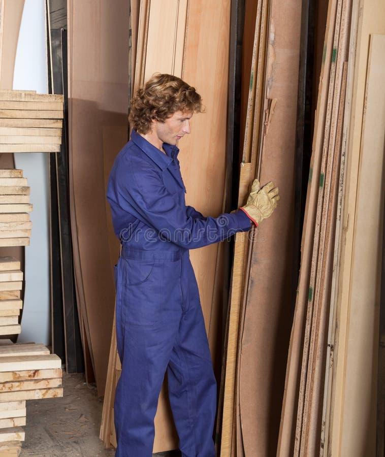 Ξυλουργός που τακτοποιεί τις ξύλινες σανίδες στο εργαστήριο στοκ φωτογραφία με δικαίωμα ελεύθερης χρήσης