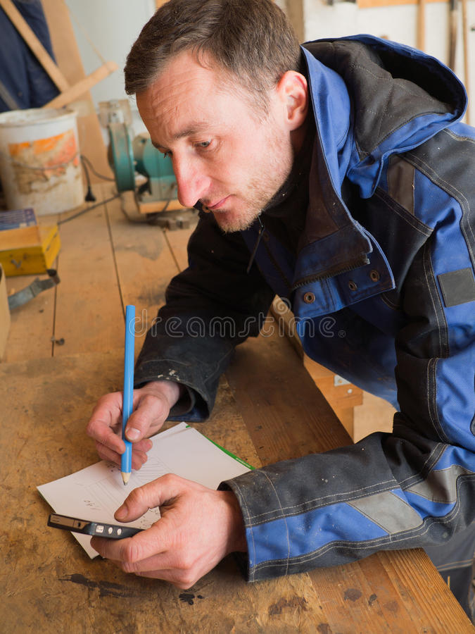 Ξυλουργός που υπολογίζει με το έξυπνος-τηλέφωνο στοκ φωτογραφίες με δικαίωμα ελεύθερης χρήσης
