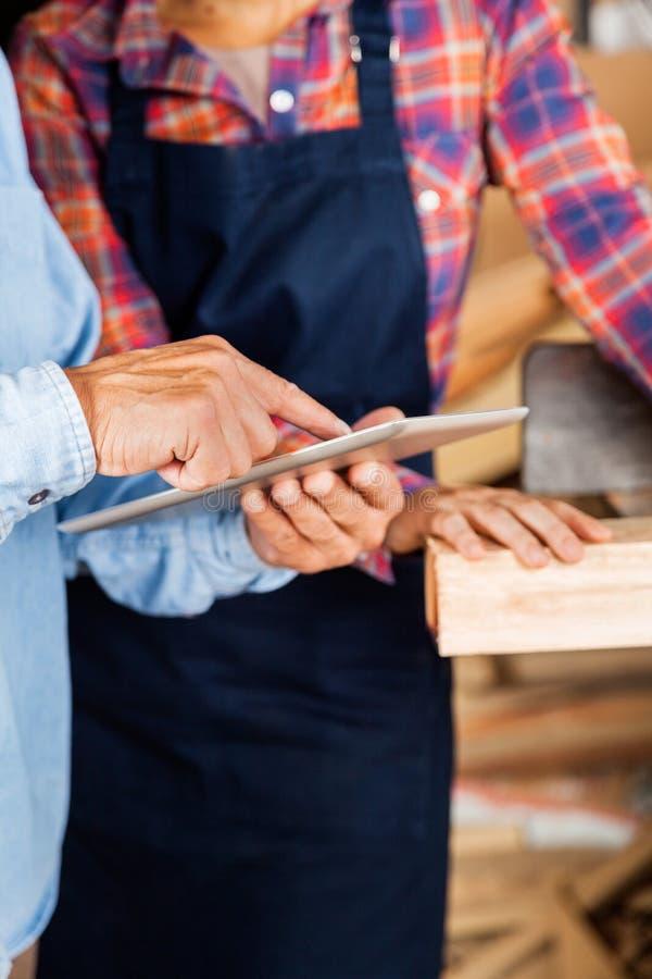 Ξυλουργός που χρησιμοποιεί την ψηφιακή ταμπλέτα εξετάζοντας στοκ φωτογραφίες