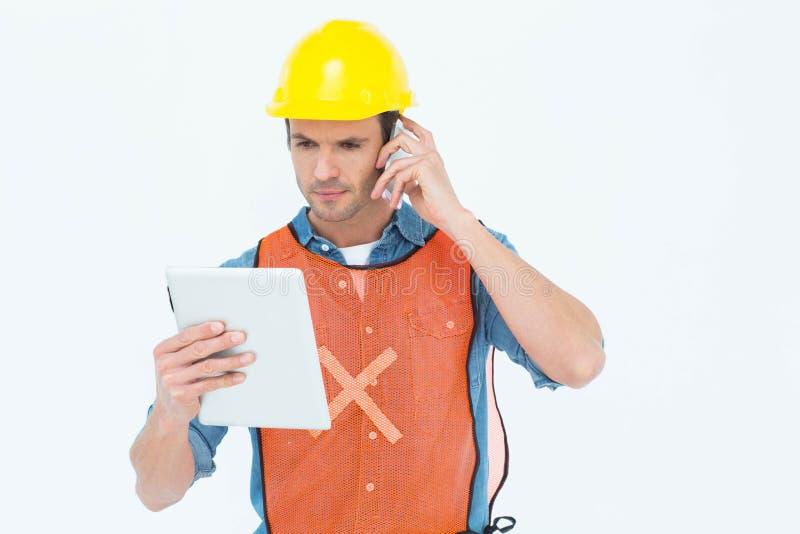 Ξυλουργός που χρησιμοποιεί την ψηφιακή ταμπλέτα και το κινητό τηλέφωνο στοκ εικόνες