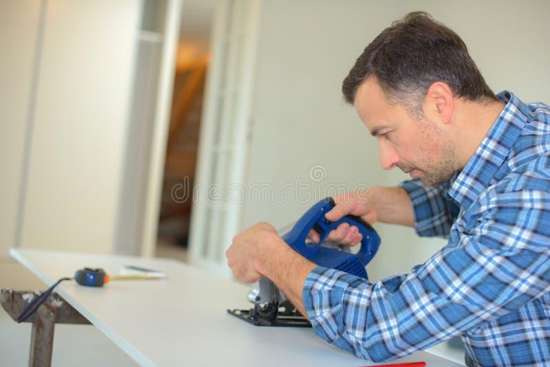 Ξυλουργός που χρησιμοποιεί το πριόνι ζωνών στοκ φωτογραφία με δικαίωμα ελεύθερης χρήσης