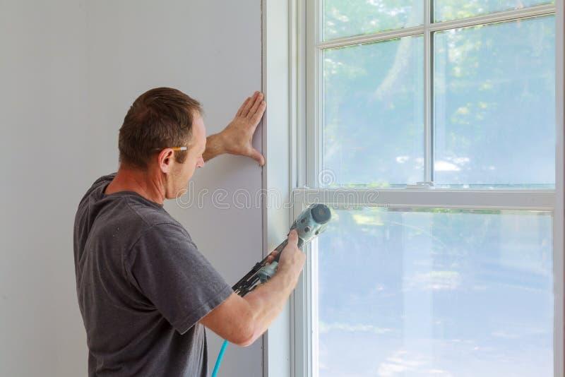 Ξυλουργός που χρησιμοποιεί το πυροβόλο όπλο καρφιών στις σχηματοποιήσεις στα παράθυρα, που πλαισιώνουν την περιποίηση, στοκ φωτογραφίες