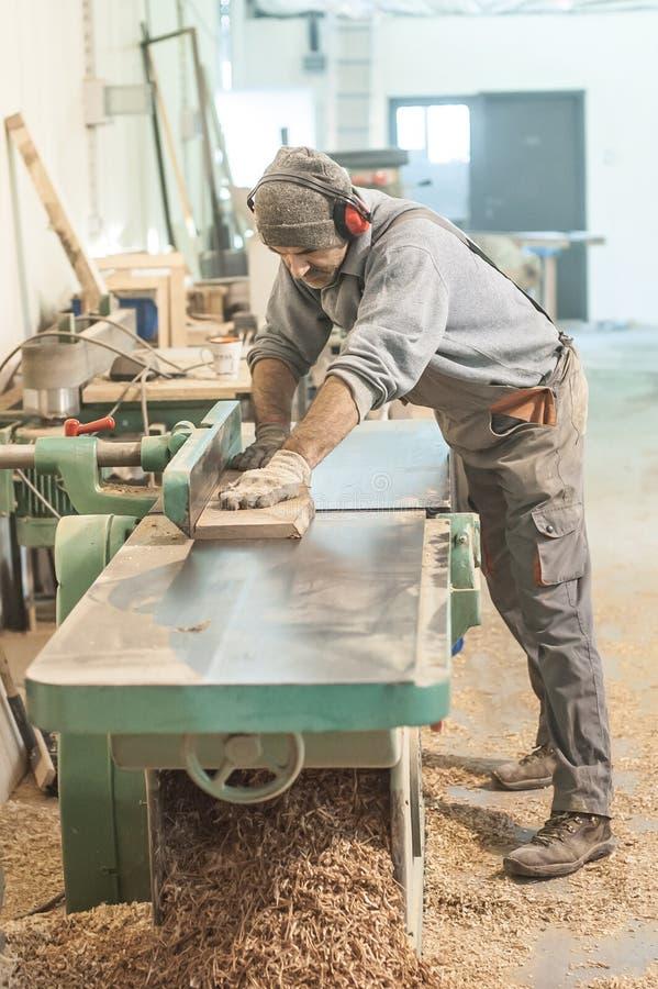 Ξυλουργός που χρησιμοποιεί sander ζωνών στοκ εικόνα