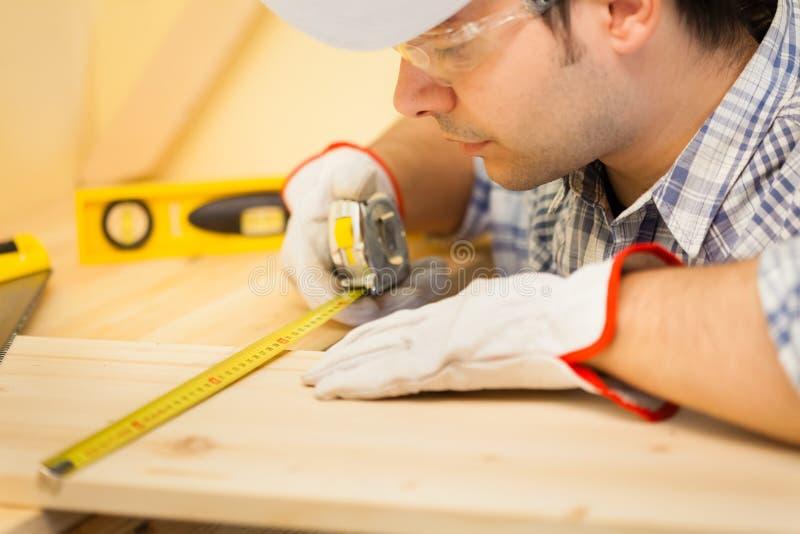 Ξυλουργός στην εργασία που χρησιμοποιεί μια μετρώντας ταινία στοκ εικόνες