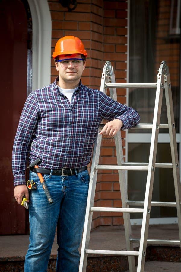 Ξυλουργός στη σκληρή τοποθέτηση καπέλων στη σκάλα βημάτων μετάλλων στοκ εικόνες