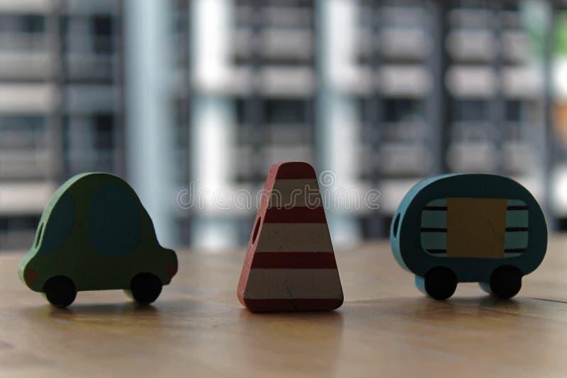 Ξύλινα αυτοκίνητα παιχνιδιών με τον πυλώνα κυκλοφορίας στον πίνακα στοκ εικόνες