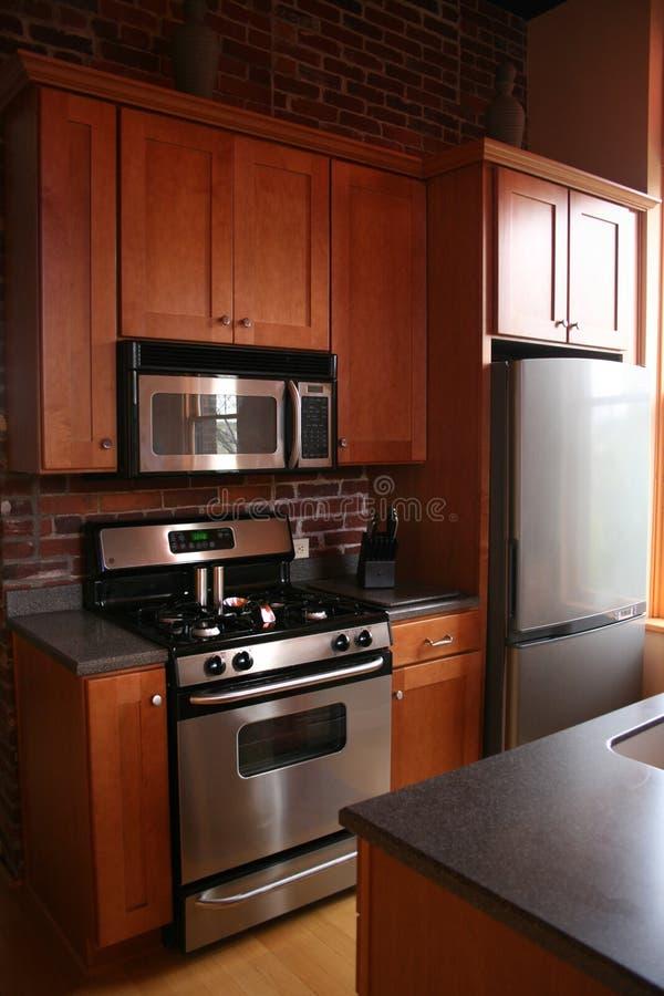 Ξύλινα γραφεία κουζινών Upscale ανοξείδωτα στοκ εικόνες