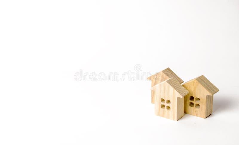 Ξύλινα ειδώλια των σπιτιών σε ένα άσπρο υπόβαθρο Διάστημα μινιμαλισμού και αντιγράφων Η έννοια της ακίνητης περιουσίας, κατοικία, στοκ φωτογραφίες με δικαίωμα ελεύθερης χρήσης