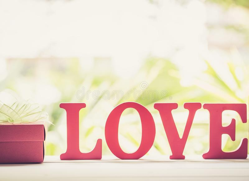 Ξύλινα κείμενο ΑΓΑΠΗΣ λέξης και κιβώτιο δώρων με την κορδέλλα τόξων στον ξύλινο επιτραπέζιο εκλεκτής ποιότητας αναδρομικό τόνο, π στοκ εικόνες με δικαίωμα ελεύθερης χρήσης