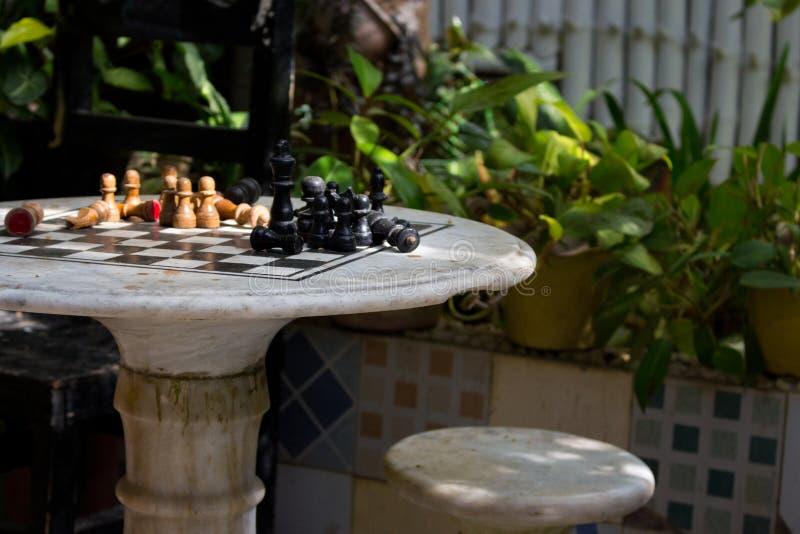 Ξύλινα κομμάτια σκακιού εν πλω στο patio με τις πράσινες εγκαταστάσεις Πίνακας σκακιού στον κήπο Υπαίθρια σκακιέρα πετρών με τους στοκ φωτογραφίες με δικαίωμα ελεύθερης χρήσης