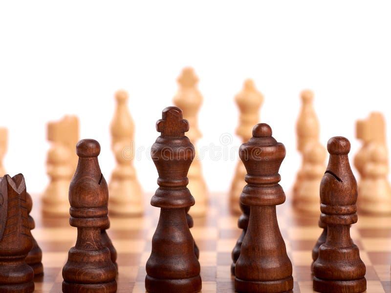 Ξύλινα κομμάτια σκακιού σε μια μονομαχία σε μια σκακιέρα Βασιλιάς, κυρία και σκοπευτές Από την ομάδα εστίασης των εχθρών o στοκ εικόνα με δικαίωμα ελεύθερης χρήσης