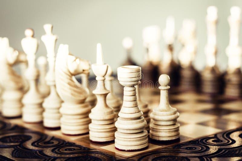 Ξύλινα κομμάτια σκακιού σε μια σκακιέρα, έννοια ηγεσίας στο άσπρο υπόβαθρο στοκ εικόνες