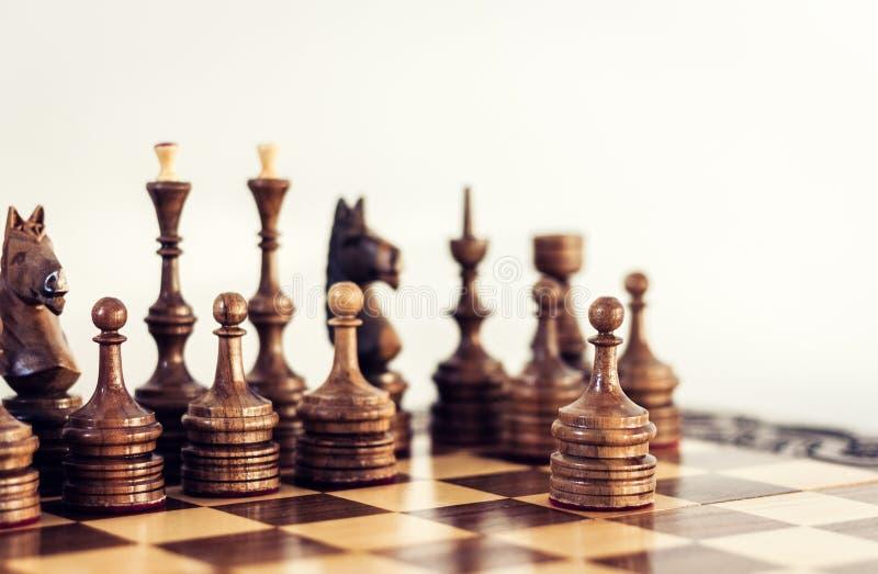 Ξύλινα κομμάτια σκακιού σε μια σκακιέρα, έννοια ηγεσίας στο άσπρο υπόβαθρο στοκ φωτογραφία