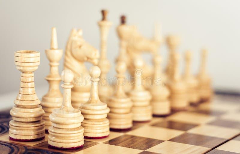 Ξύλινα κομμάτια σκακιού σε μια σκακιέρα, έννοια ηγεσίας στο άσπρο υπόβαθρο στοκ εικόνα με δικαίωμα ελεύθερης χρήσης