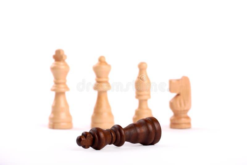 Ξύλινα κομμάτια σκακιού στη μονομαχία Λευκοί βασιλιάς, κυρία και σκοπευτές με το άλογο Ο νικημένος μαύρος βασιλιάς παραδίνει στην στοκ εικόνα με δικαίωμα ελεύθερης χρήσης