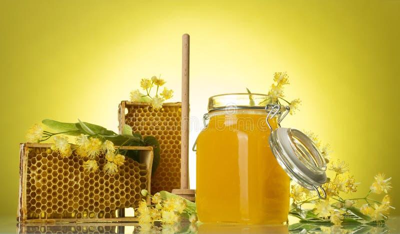 Ξύλινα πλαίσια με την κηρήθρα και το μέλι κεριών στο βάζο, στο κίτρινο υπόβαθρο στοκ φωτογραφία με δικαίωμα ελεύθερης χρήσης