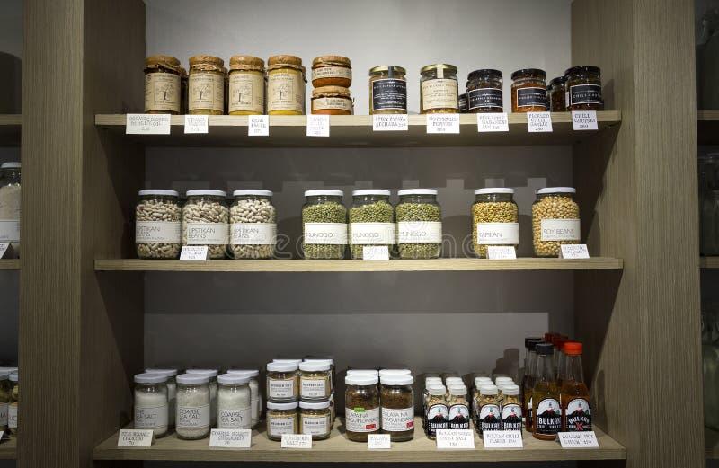 Ξύλινα ράφια βάζα ενός στα πλήρη og καταστημάτων και μπουκάλια με τα φυσικά οργανικά προϊόντα στην επίδειξη στοκ εικόνες με δικαίωμα ελεύθερης χρήσης