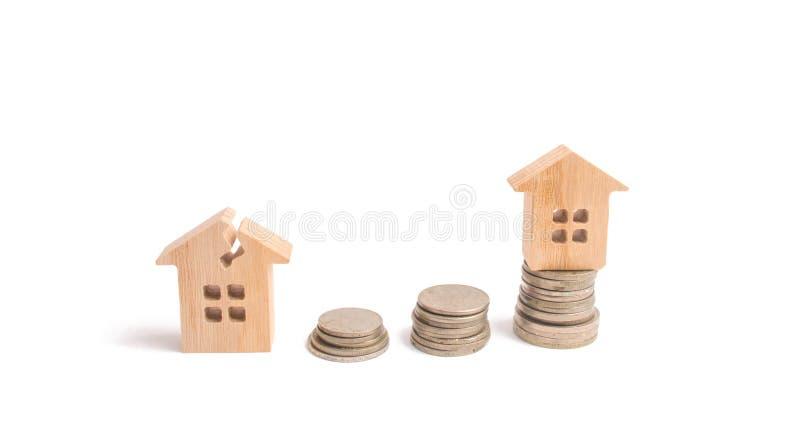 Ξύλινα σπίτια στους σωρούς των νομισμάτων Επένδυση στην επισκευή και την αποκατάσταση της κατοικίας εξέταση αύξηση χρημάτων στοκ εικόνα
