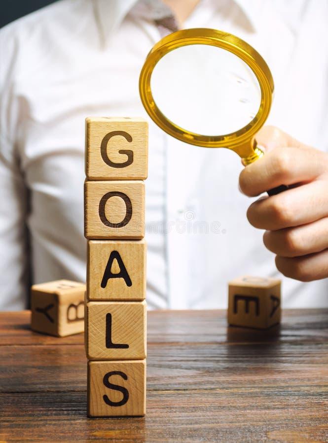 Ξύλινα τετράγωνα με τη λέξη Γκολ και επιχειρηματίας Η έννοια της επίτευξης του επιχειρηματικού στόχου Επίτευξη νέων υψών Εκτέλεση στοκ εικόνες με δικαίωμα ελεύθερης χρήσης