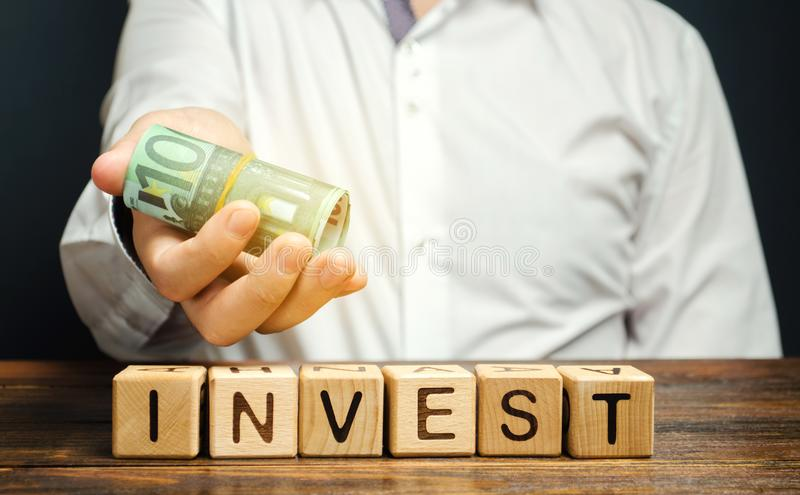 Ξύλινα τετράγωνα με τη λέξη Επενδύστε και χρήματα στα χέρια ενός επιχειρηματία Έννοια της επένδυσης σε επιχειρηματικό σχέδιο Οικο στοκ φωτογραφία