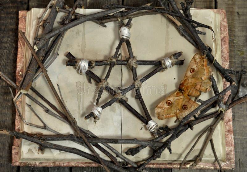 Ξύλινα pentagram και σύμβολο του θανάτου - σκώρος, στο ανοικτό βιβλίο με τις κενές σελίδες, τοπ άποψη στοκ εικόνα