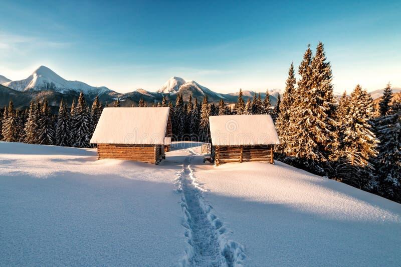 Ξύλινες καλύβες σε χειμερινά βουνά την ανατολή του ήλιου στοκ φωτογραφία