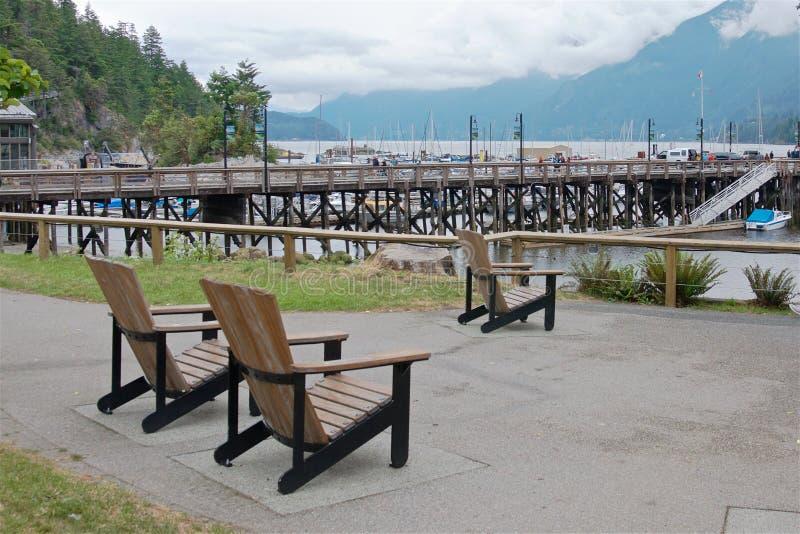 Ξύλινες καρέκλες στην παραλία κοντά στην αποβάθρα, πεταλοειδής κόλπος στοκ φωτογραφία με δικαίωμα ελεύθερης χρήσης