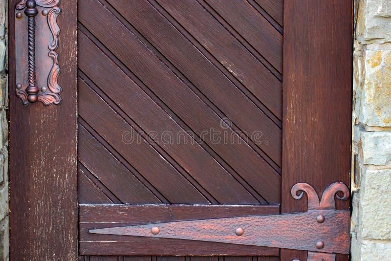 Ξύλινες πόρτες με το σφυρηλατημένο κομμάτι σιδήρου Παλαιός ξύλινος παλαιός ξύλινος στοκ φωτογραφίες