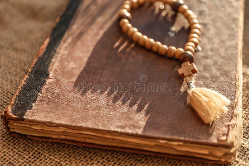 Ξύλινες rosary χάντρες και παλαιό βιβλίο στοκ φωτογραφία με δικαίωμα ελεύθερης χρήσης