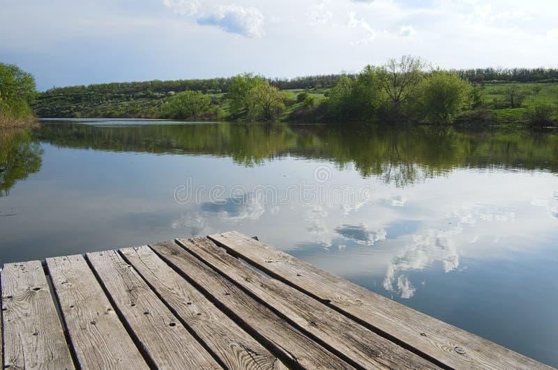 Ξύλινη αποβάθρα σε έναν ποταμό Ουρανός που απεικονίζεται νεφελώδης στο νερό στοκ φωτογραφίες