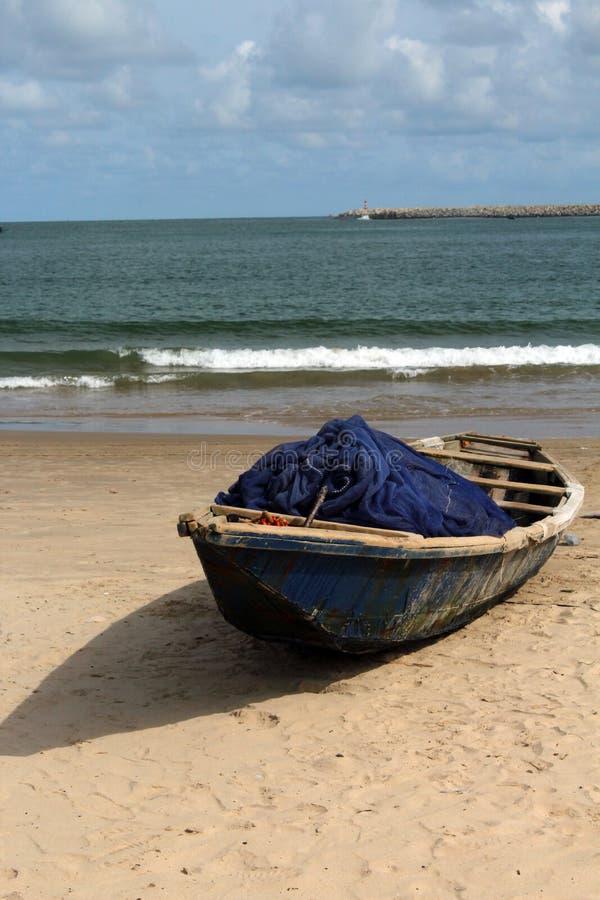 Ξύλινη βάρκα συντριμμιών με το δίχτυ του ψαρέματος από μια πλευρά παρα στοκ φωτογραφίες με δικαίωμα ελεύθερης χρήσης