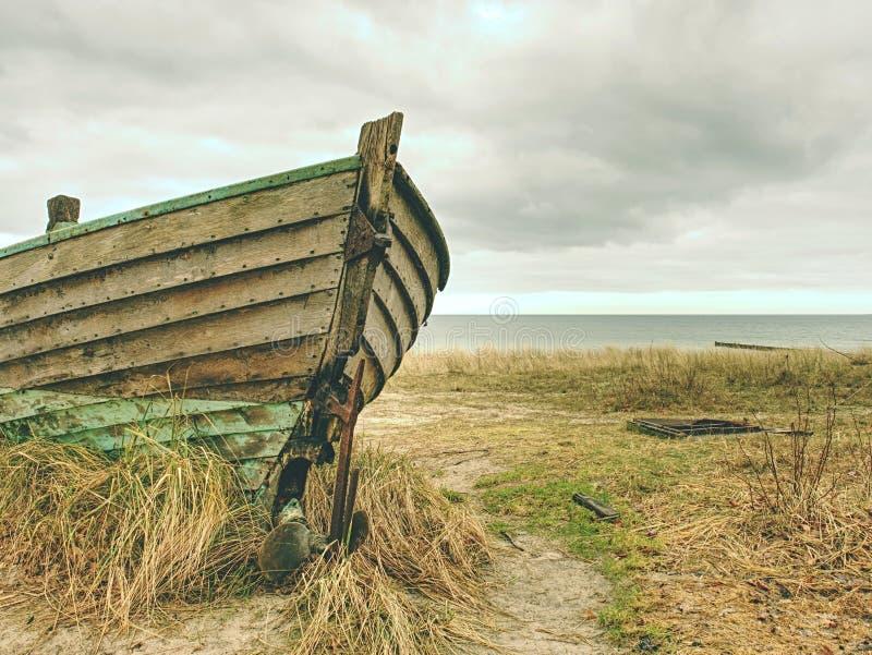 Ξύλινη βάρκα ψαράδων Σπασμένη εγκαταλειμμένη βάρκα στην άμμο του κόλπου θάλασσας στοκ εικόνα