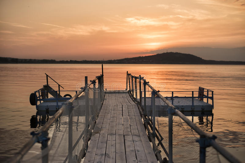 Ξύλινη γέφυρα στην παραλία και όμορφο ηλιοβασίλεμα κοντά στη θάλασσα στοκ εικόνες