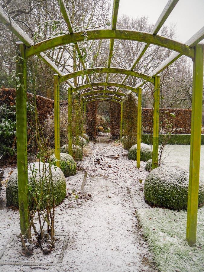 Ξύλινη δομή περγκολών κατά τη διάρκεια του χειμώνα σε έναν χιονισμένο κήπο στοκ φωτογραφία με δικαίωμα ελεύθερης χρήσης