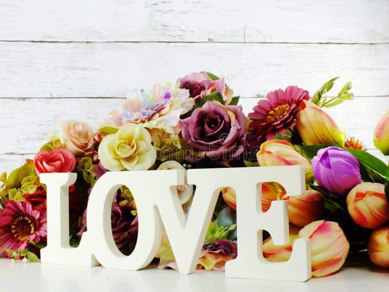 Ξύλινη επιστολή λέξης αγάπης με το ντεκόρ τεχνητών λουλουδιών στοκ εικόνες