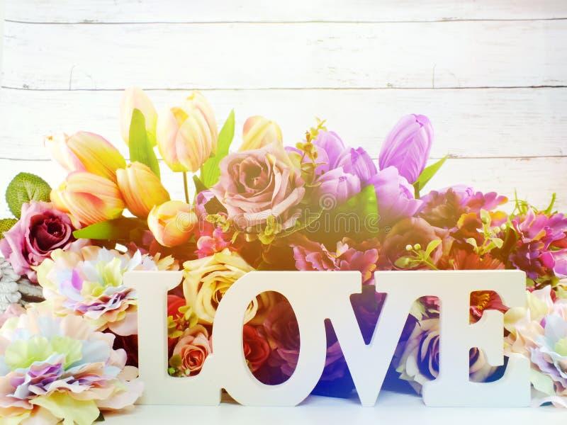 Ξύλινη επιστολή λέξης αγάπης με το ντεκόρ τεχνητών λουλουδιών στοκ εικόνα