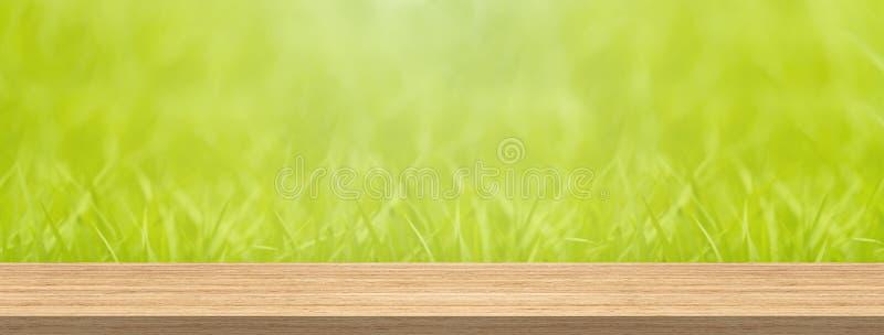 Ξύλινη επιτραπέζια κορυφή και πράσινη χλόη θαμπάδων για το μέγεθος εμβλημάτων montage προϊόντων και επίδειξης στοκ φωτογραφίες