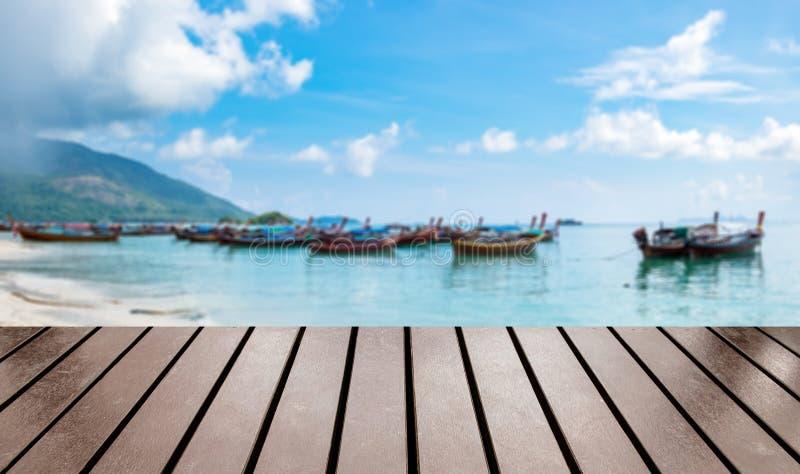 Ξύλινη επιτραπέζια κορυφή στη θολωμένη θάλασσας βάρκα ουρών ομάδας μακριά στοκ εικόνες με δικαίωμα ελεύθερης χρήσης