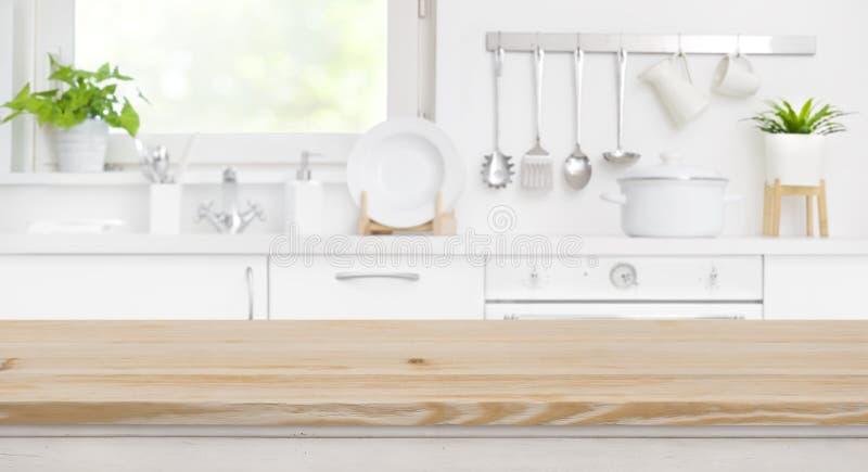 Ξύλινη επιτραπέζια κορυφή στο δωμάτιο κουζινών θαμπάδων και το υπόβαθρο παραθύρων στοκ εικόνες
