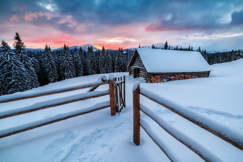 Ξύλινη καμπίνα στα χειμερινά βουνά το ηλιοβασίλεμα στοκ φωτογραφία