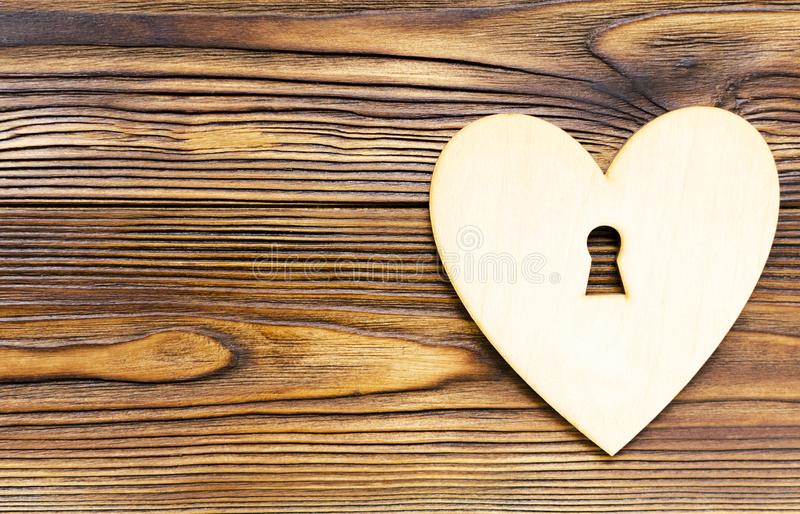 Ξύλινη καρδιά με την κλειδαρότρυπα στο ξύλινο υπόβαθρο με το διάστημα αντιγράφων στοκ φωτογραφία